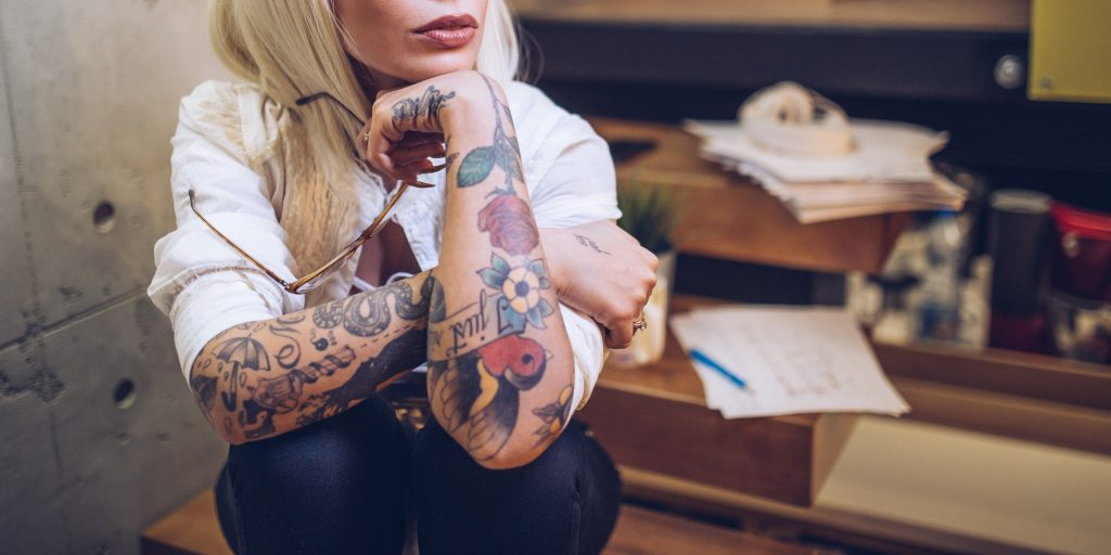 tattooed woman working 1 1024x512 - Things to Know About People With Tattoos
